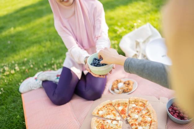 Mulheres comendo mirtilos. vista superior de mulheres comendo mirtilos enquanto estão sentadas na grama no verão