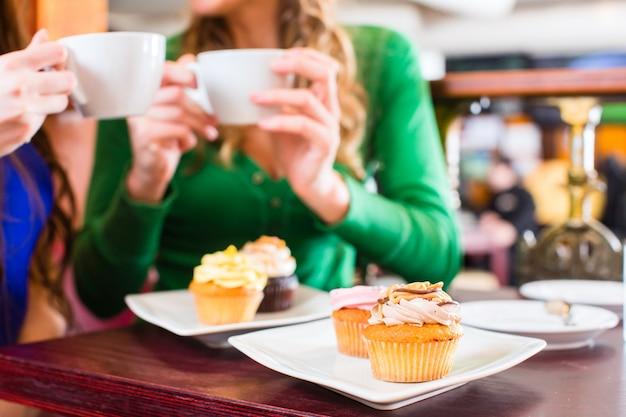 Mulheres, comendo, muffins, enquanto, café, bebendo