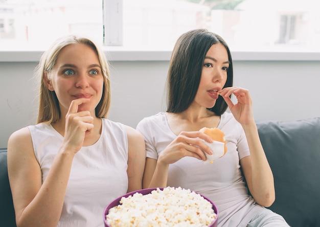 Mulheres comendo pipoca e hambúrguer e assistindo tv