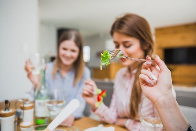 Mulheres, comendo salada, em, sala de estar