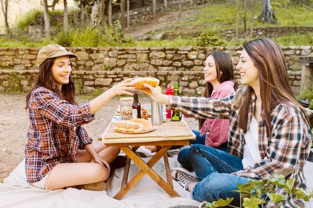 Mulheres, comer, cachorro quente, em, natureza