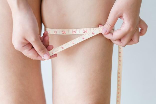 Mulheres como segurando e empurrando a celulite da pele das pernas com testador de gordura corporal pessoal.