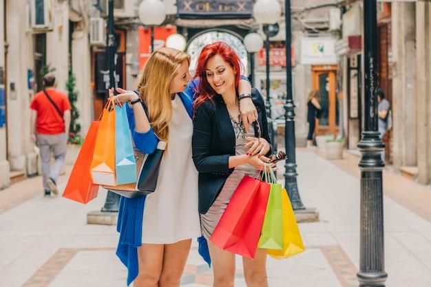 Mulheres compradoras abraçando na rua
