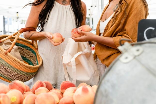 Mulheres comprando pêssego, comprando no mercado de frutas frescas