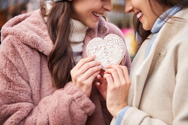 Mulheres conectadas com um biscoito de gengibre em formato de coração