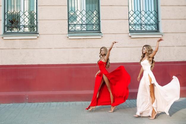 Mulheres confiantes e elegantes, levantando seus elegantes vestidos de noite