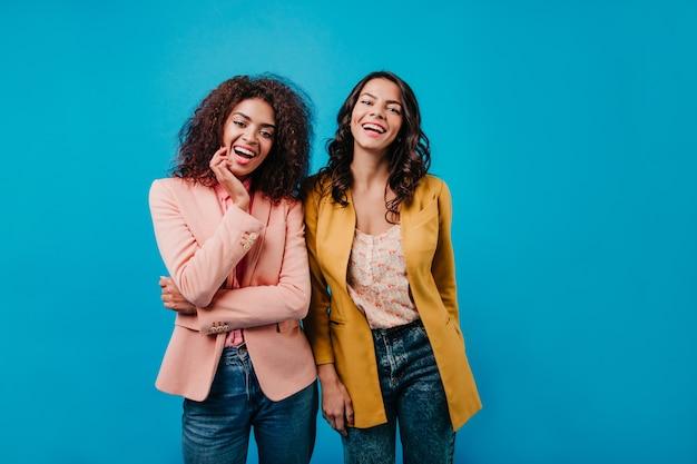 Mulheres confiantes em pé na parede azul