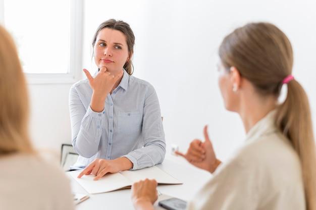 Mulheres conversando à mesa usando linguagem de sinais