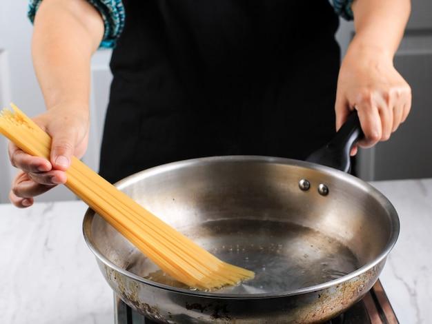 Mulheres cozinhando espaguete na panela de água fervente na cozinha. processo e preparação de comida caseira