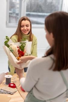 Mulheres criando um buquê de flores