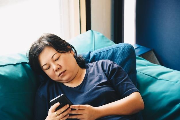 Mulheres da ásia 40 anos segurando smartphone pensando no sofá