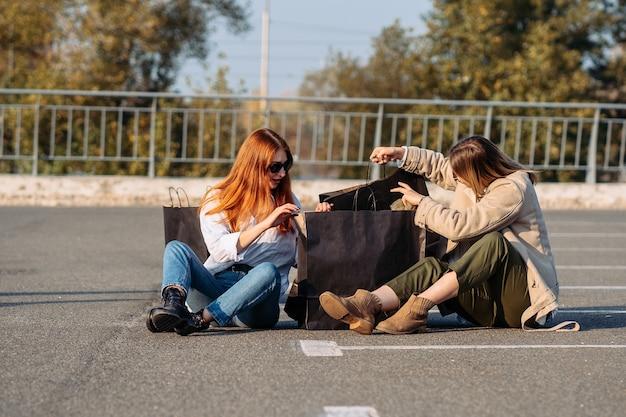 Mulheres da moda jovem com sacolas de compras sentadas no estacionamento