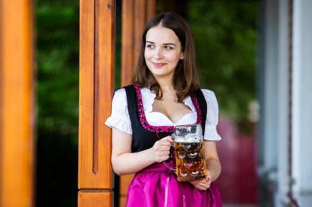 Mulheres da oktoberfest com um vestido tradicional da baviera segurando canecas de cerveja