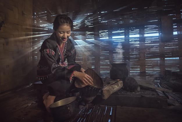 Mulheres da vila de laos que cozinham na cozinha tradicional na manhã.