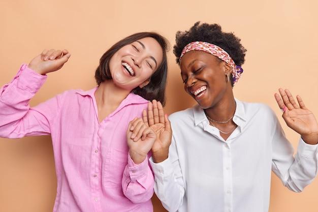 Mulheres dançam e se movem energicamente ao ritmo da música vestidas casualmente e tolas isoladas em bege