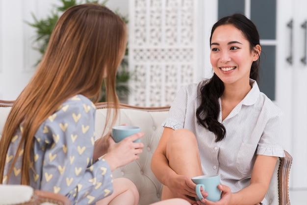 Mulheres de alto ângulo no sofá conversando