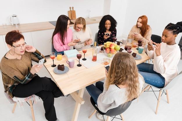 Mulheres de alto ângulo, olhando em seus telefones