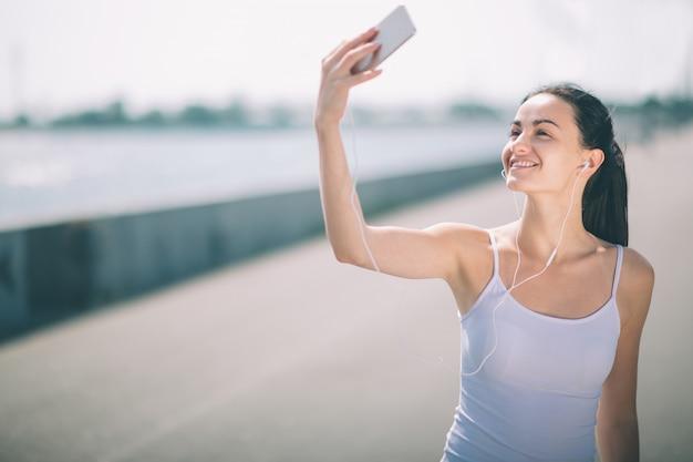 Mulheres de aptidão exercitando e esticando ao ar livre e fazendo selfie
