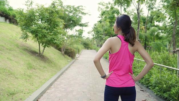 Mulheres de atleta asiático jovem bonita saudável em aquecimento de pernas de roupa de esportes