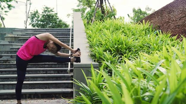 Mulheres de atleta asiático jovem bonita saudável em esportes roupa pernas aquecimento e alongamento