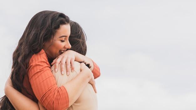 Mulheres de baixo ângulo abraçando