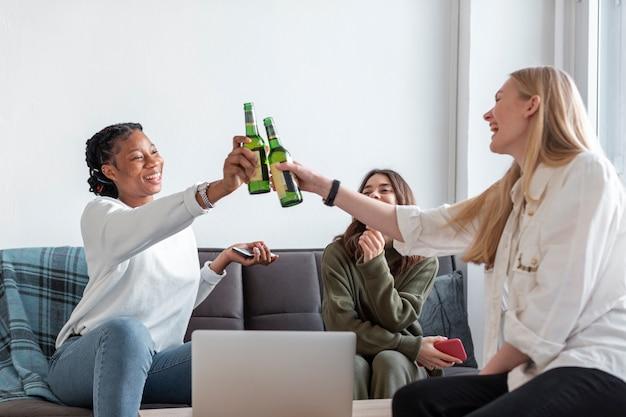 Mulheres de baixo ângulo em casa brindando