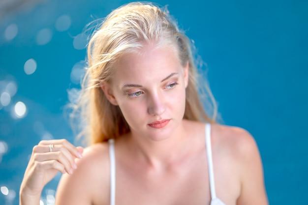 Mulheres de biquíni branco com rosto sorridente, usando chapéu na beira da piscina no verão