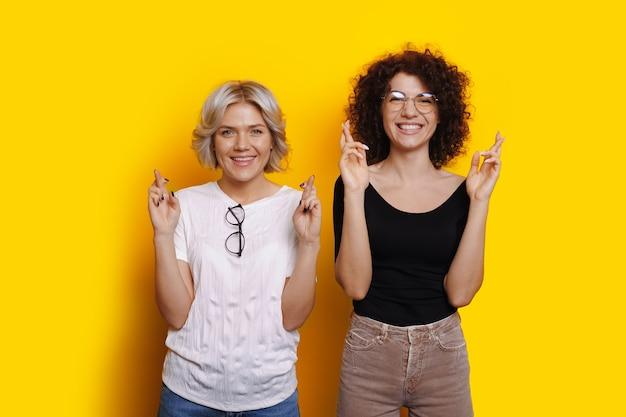 Mulheres de cabelos cacheados caucasianos sonham com algo cruzando os dedos em uma parede amarela com espaço livre