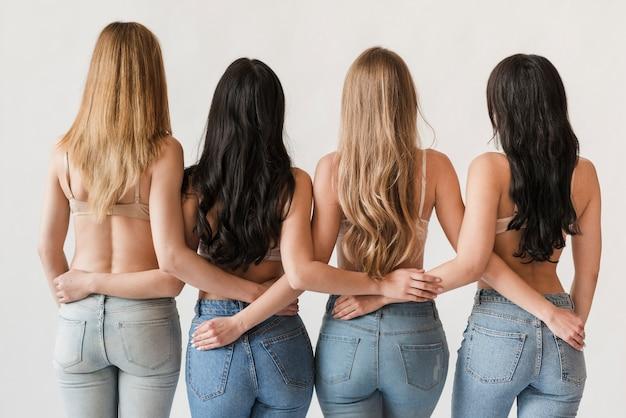 Mulheres de cabelos compridos, vestindo sutiãs ficar juntos e abraçando