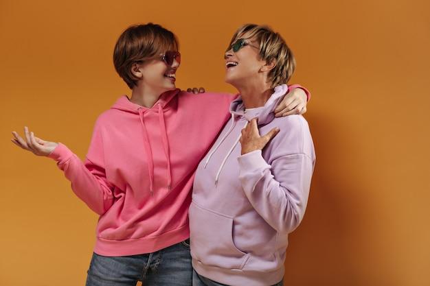 Mulheres de cabelos curtos com óculos de sol em modernos moletons lilás e rosa com capuz e jeans, sorrindo e se abraçando em um pano de fundo laranja isolado.