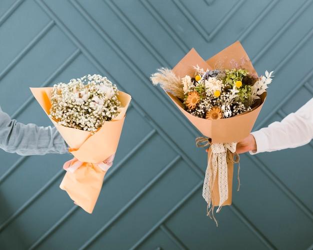 Mulheres de close-up segurando buquês de flores bonitas