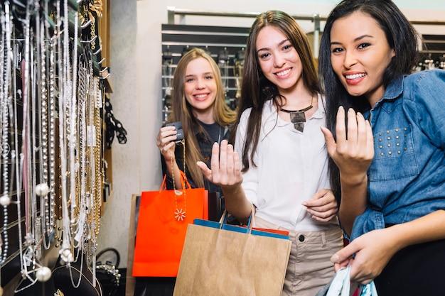 Mulheres de conteúdo gesticulando na câmera na loja