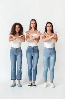 Mulheres de diferentes nacionalidades, mostrando o gesto stop em branco. conceito de racismo