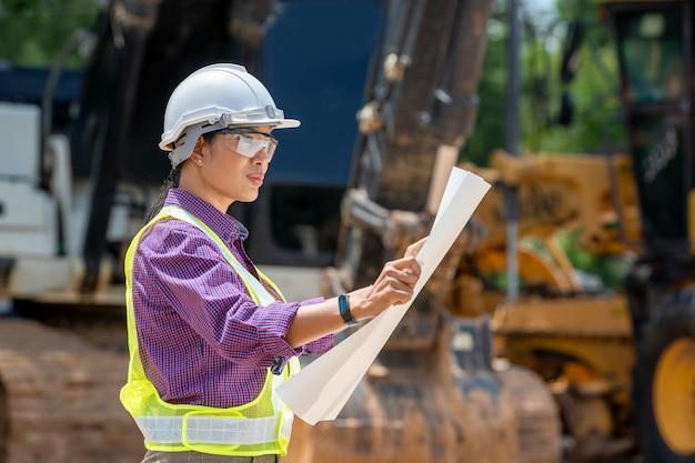 Mulheres de engenheiro ou arquiteto segurando plantas com caminhão carregador no canteiro de obras, veículo de construção de engenharia na área de trabalho.