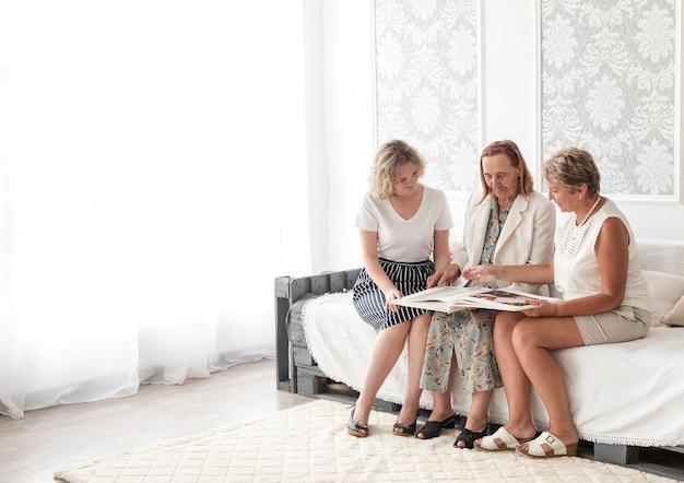 Mulheres de geração multi olhando o álbum de fotos juntos enquanto está sentado no sofá