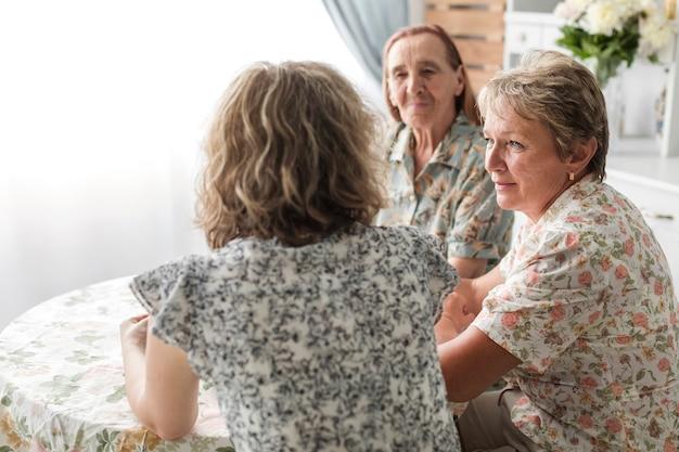 Mulheres de geração multi sentado na cozinha tomando café da manhã