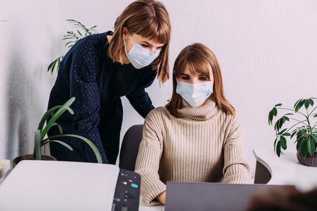Mulheres de irmãs gêmeas lindas com uma máscara protetora médica trabalhando juntos em um escritório leve rodeado por plantas. conceito covid-19.