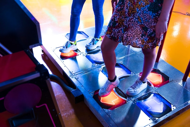 Mulheres de lado jogando fliperama