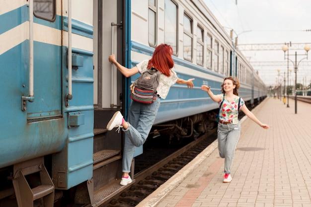Mulheres de longo alcance pegando o trem