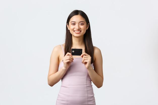 Mulheres de luxo, conceito de festa e feriados. feliz garota asiática bonita rica em vestido de noite, mostrando a ela
