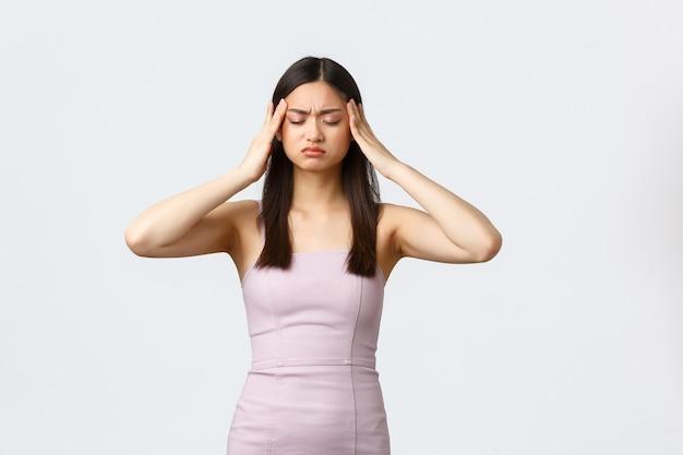 Mulheres de luxo, conceito de festa e feriados. mulher asiática jovem angustiada em um vestido de noite, tendo enxaqueca, tocando a cabeça e fazendo uma careta de dor