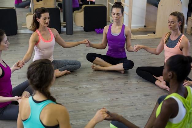 Mulheres de mãos dadas e meditando