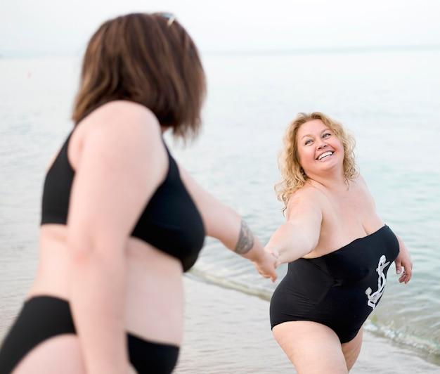 Mulheres de mãos dadas na praia