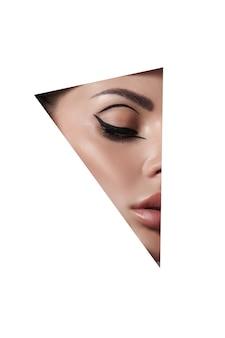 Mulheres de maquiagem de beleza, sobrancelhas, cílios e lábios em um fundo branco de papel de buraco triangular. maquiagem profissional de beleza, lugar para texto, espaço de cópia