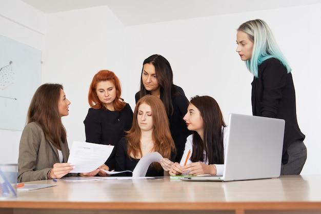 Mulheres de negócio de sorriso novas que trabalham o projeto novo no escritório.
