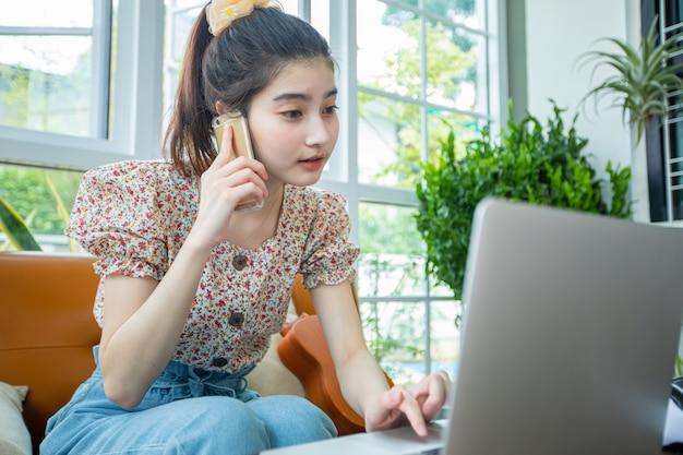 Mulheres de negócios asiáticas estão usando notebooks e celulares para reuniões on-line e trabalhando em casa