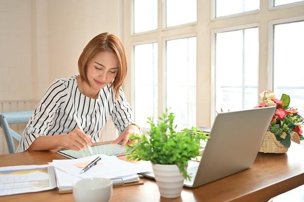 Mulheres de negócios asiáticas que trabalham com tablet digital e caneta.