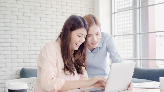 Mulheres de negócios asiáticos criativos inteligentes atraentes em casual desgaste inteligente trabalhando no laptop enquanto está sentado