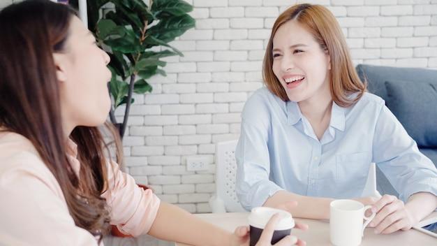 Mulheres de negócios asiáticos desfrutando de beber café quente, discutir sobre o trabalho e chit chat fofoca
