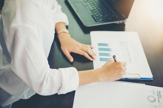 Mulheres de negócios asiáticos trabalhando e gráficos de análise no escritório
